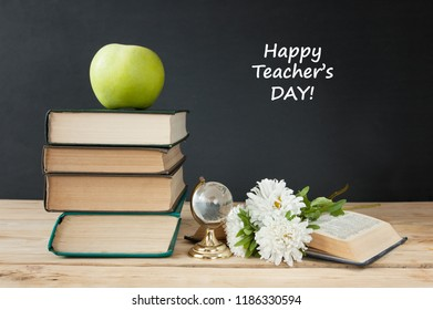 Happy teacher's day, book pile with apple and globe, still life