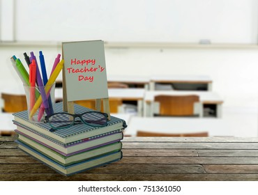 Happy Teacher's day with book stack, greeting card in picture frame, eyeglasses, pens over blurred classroom, white board, school and education background