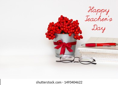Happy Teacher's day greeting card - bouquet of red mountain ash in flower pot with satin ribbon, pile of notebooks, glasses and pen on white background. International school Teacher Day.