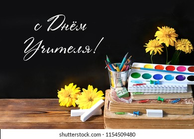 """happy teacher's day"" inscription in Russian language. Teachers day greeting card with fresh flowers, books and stationery. Text teacher's day on the school blackboard."