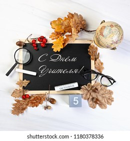 """Happy teacher's day"" inscription in Russian language. Teachers day greeting card. autumn leaves, books and stationery. Text teacher's day on the school blackboard."