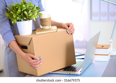 Happy team of businesspeople moving office, packing boxes, smiling