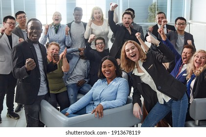 happy team of diverse corporate employees in the office lobby.