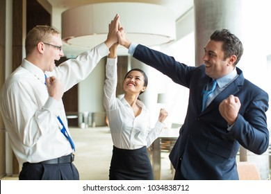 Happy team giving hi-five after successful work