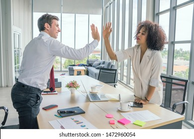 Happy team giving hi-five after successful work.Businessman giving hi five/ touching hands with co worker after finish work and Completed the work perfectly, as expected.