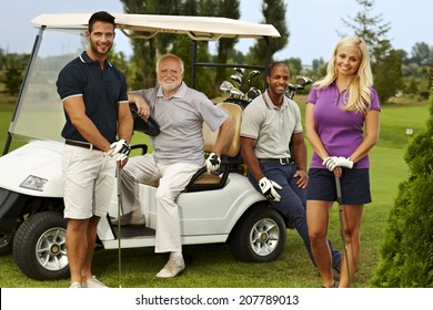 Happy team of golfers ready to play, standing and sitting around golf cart, smiling, looking at camera.