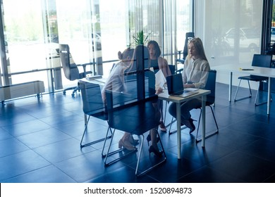 happy team group successful females listening to colleague at meeting in modern office panoramic windows