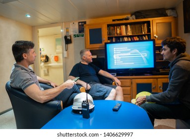 Happy team of ship officers watch TV onboard of vessel. TV, recreation and internet at sea