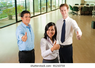 Happy team of three diverse business people, Asian, Hispanic and Caucasian, standing, displaying thumbs up for approval while looking at camera seen down from high angle in large office. Horizontal