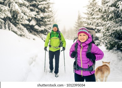 Happy teamwork couple hikers trekking in white winter woods and mountains. Young people walking on snowy trail with backpacks, healthy lifestyle adventure, camping and hiking, Poland.