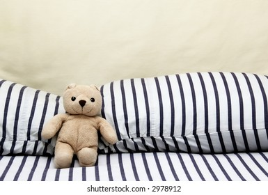 Happy teddy bear relaxing on comfortable bed