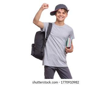 Happy teen boy with books and backpack, isolated on white background. Cheerful child with cap making greeting gesture. Emotional portrait of teenager guy Back to school.