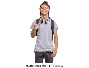 Happy teen boy in cap with headphones and backpack, isolated on white background. Cheerful child laughing and looking at camera. Emotional portrait of handsome teenager guy Back to school.