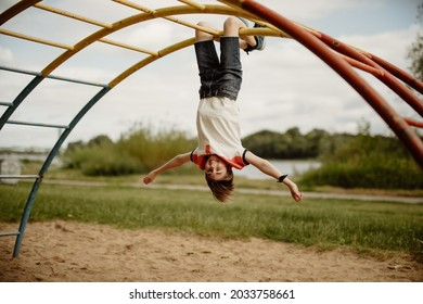 happy teen boy enjoy childhood by hanging upside down from pole of a climbing frame on playground