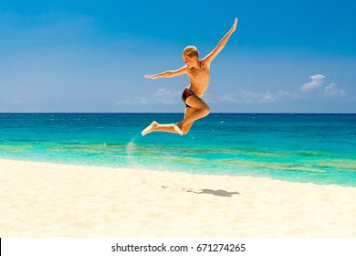 Happy teen boy having fun on the tropical beach. Summer vacation concept