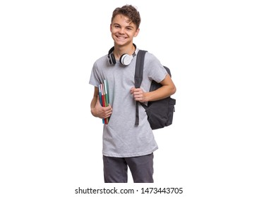 Happy teen boy with headphones and backpack holding books, isolated on white background. Smiling child looking at camera. Emotional portrait of handsome teenager guy Back to school.