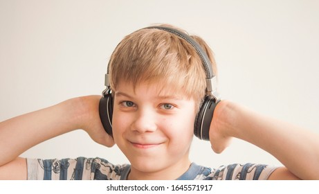 Happy teen boy is listening music with headphones