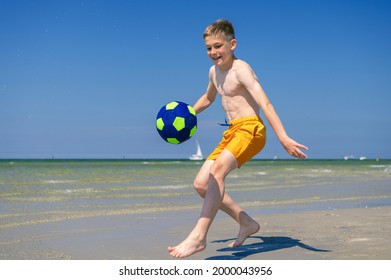 Happy teen boy playing with ball on beach at summer sunny day with blue sky on background