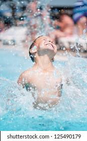 Happy teen boy in pool at aqua park