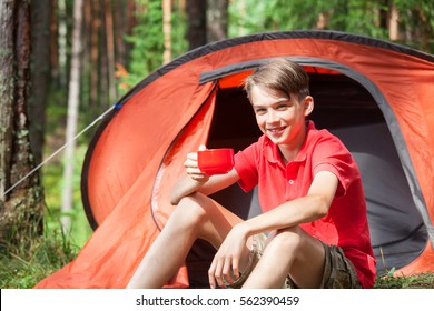Happy teen boy sitting at a camping tent in a summer forest holding a cup of drink or soup looking at camera smiling