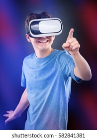 Happy teen boy wearing virtual reality goggles playing video games, on colorful bokeh background. Cheerful smiling looking in VR glasses and gesturing with his hand. Child experiencing 3D gadget
