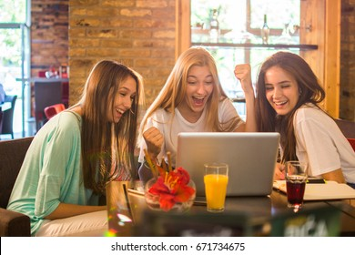 Happy teen friends using laptop together in cafe.