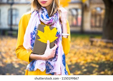 Happy teen girl with book smile during walking on autumn park. Fall concept