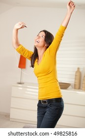 Happy teen girl dancing at home with earphones holding mp3 player smiling.