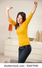 Happy teen girl dancing at home with earphones holding mp3 player smiling at camera.