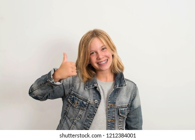 Happy teen girl with dental brace showing thumb up gesture.