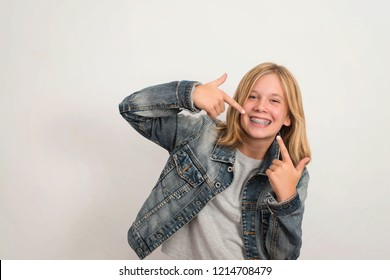 Happy teen girl with dental brace showing, pointing on her teeth.