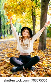 Happy teen girl enjoy beautiful autumn park. Woman walking on a street