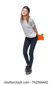 Happy teen girl in full length holding skate board looking to the side at blank copy space, isolated on white background