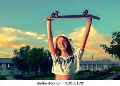 Happy teen girl with her skateboard up in the air, vintage toned image