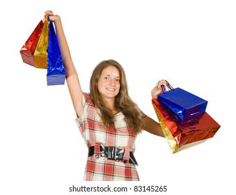Happy teen girl holding shopping bags. Isolated over a white background