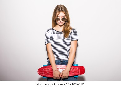 Happy teen girl holding skate board isolated on white