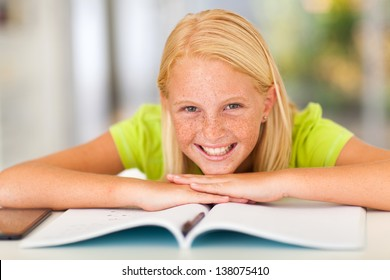 happy teen girl lying on book at home