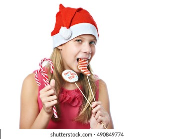 Happy teen girl in red cap eating Christmas cookie isolated white