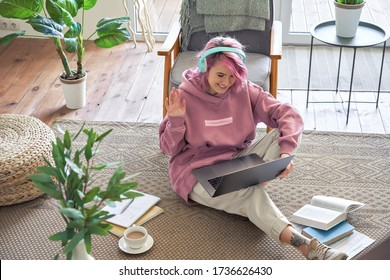 Happy teen girl school college student pink hair wear headphone waving hand video conference calling on laptop computer sit on floor distance learn zoom online virtual meeting at home office. Top view