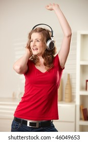 Happy teen girl singing and dancing with headphones at home smiling.