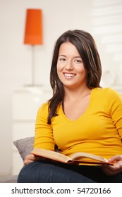 Happy teen girl sitting on sofa at home, reading book, looking at camera, smiling.