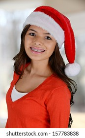 Happy teen girl smiling while wearing a santa hat