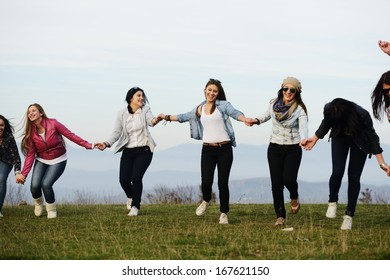 Happy teen girls having good fun time outdoors running and jumping
