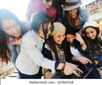 Happy teen girls having good fun time outdoors (with harsh sunlight effect)