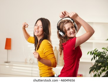 Happy teen girls listening to music via headphone and earphone having fun together at home dancing smiling at camera.