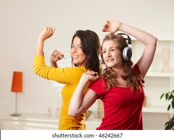 Happy teen girls listening to music having fun together at home dancing smiling.