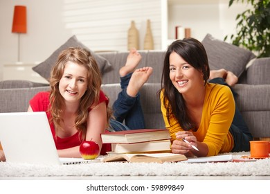 Happy teen girls lying on floor studying with laptop and books smiling at camera at home.?