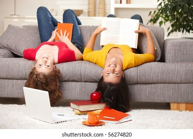 Happy teen girls sitting upside down on sofa smiling looking at camera holding books.