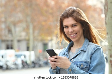Happy teen holding a cell phone looking at you in the street