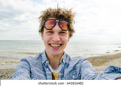 Happy teen selfie sea, beautiful young man near sea, smiling teenager on the vacation